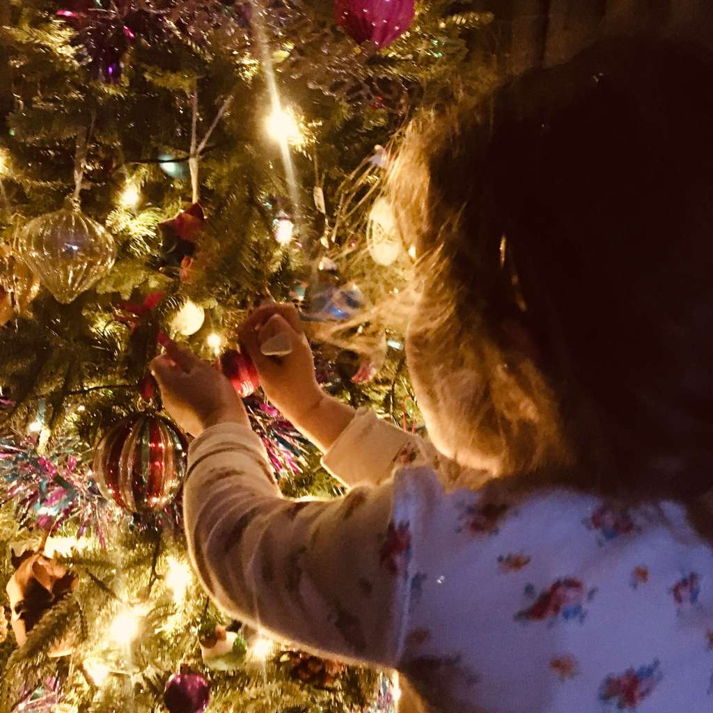 A girl places a Christmas decoration on an illuminated Christmas tree