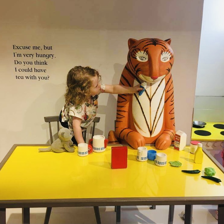 A young girl enjoys the 2019 Tiger Who Came To Tea exhibition at the Discover Children's Story Centre in Stratford, sitting at the table with the tiger from Judith Kerr's 1968 classic children's book