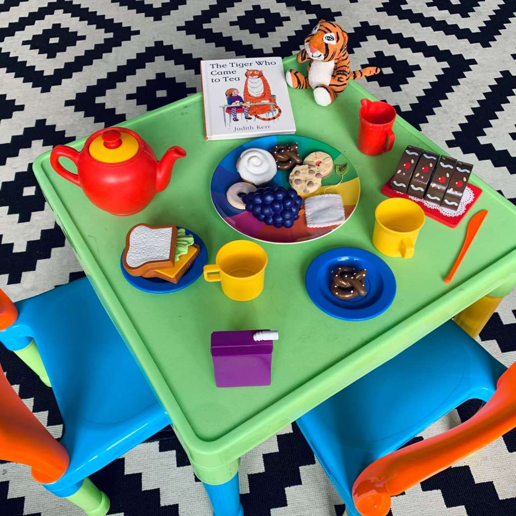 A child's table is set with pretend crockery, cutlery and food, as well as a copy of Judith Kerr's The Tiger Who Came to Tea and a cuddly toy version of the eponymous tiger