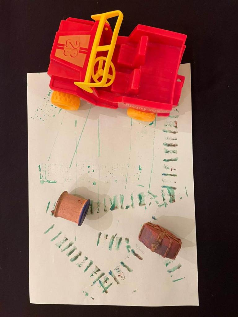 A painting activity is shown, using a toy car and an empty cotton reels to make paint tracks on paper