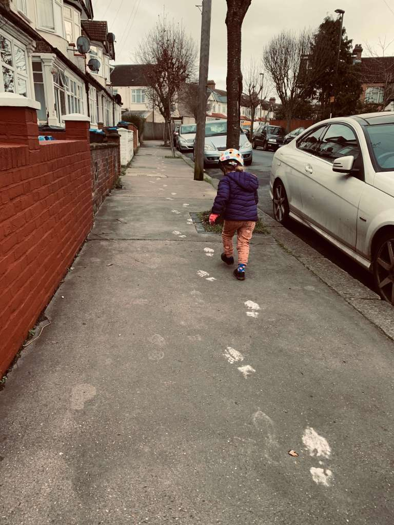 A girl follows a trail of white footprints up a residential street