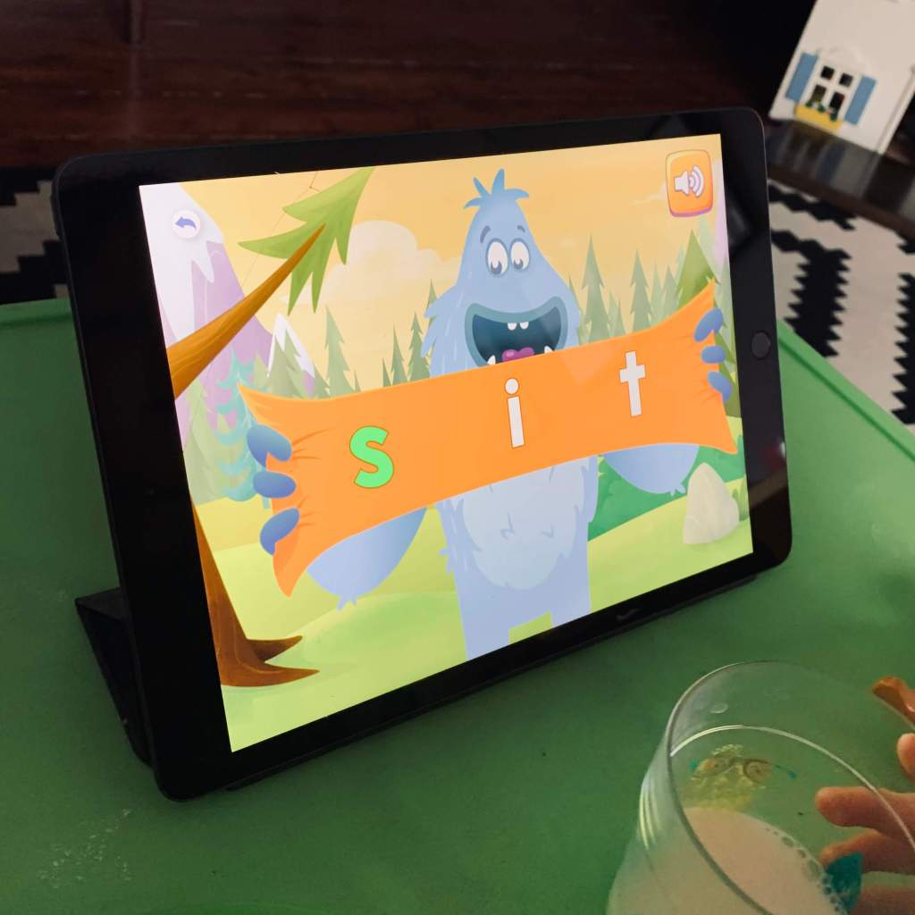 An iPad shows an image from a lesson on the Reading Eggs app