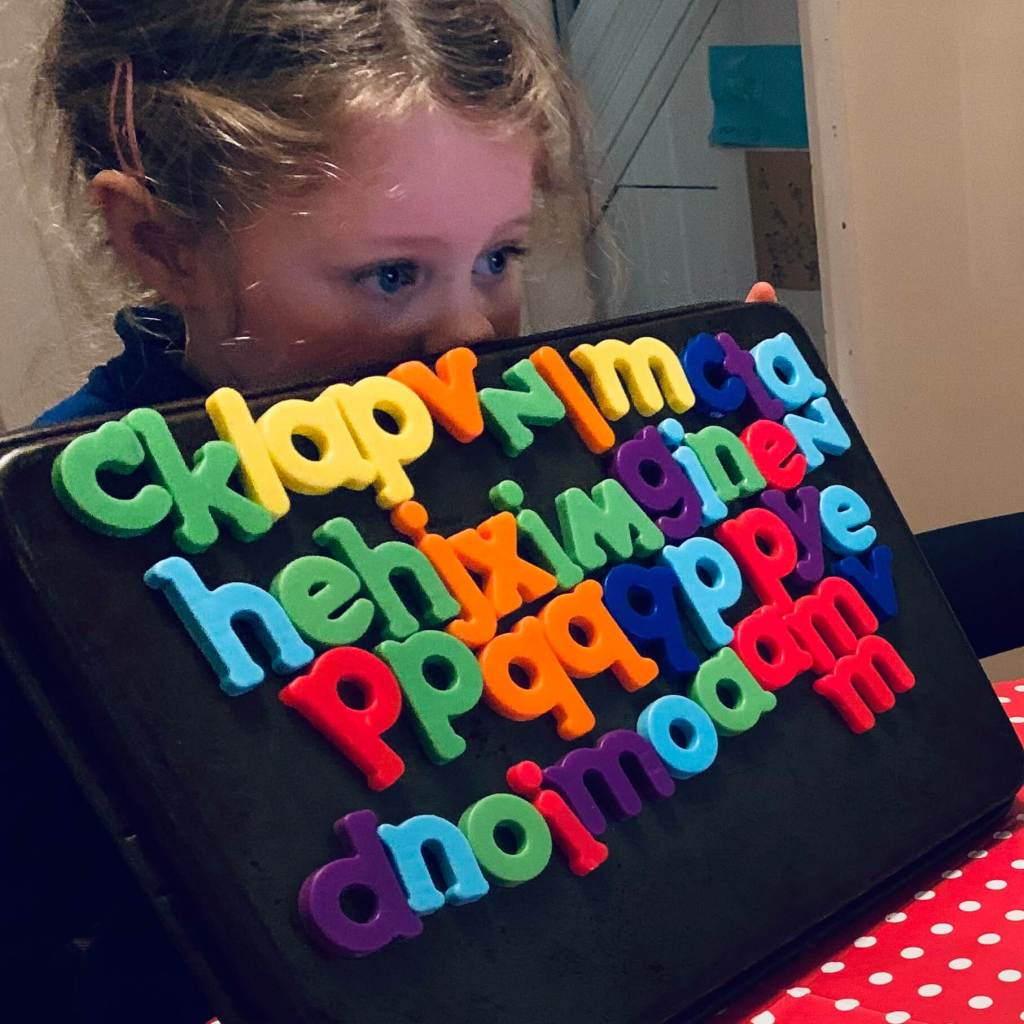 A girl holds up a metal baking tray covered by magnetic letters