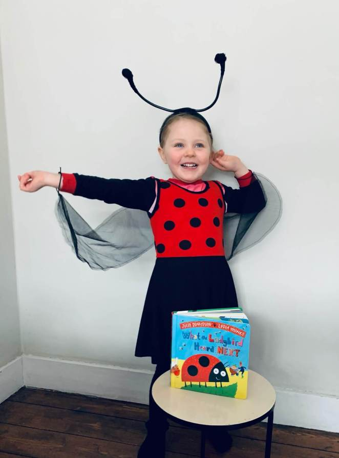 A girl is dressed for World Book Day as the ladybird from What the Ladybird Heard by Julia Donaldson and Lydia Monks