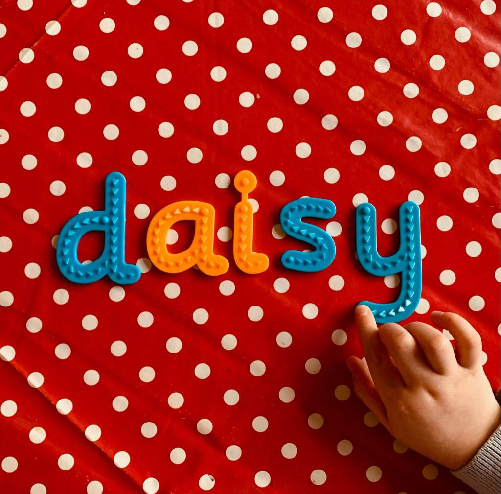 A preschooler uses tactile letters shapes to spell her name: Daisy