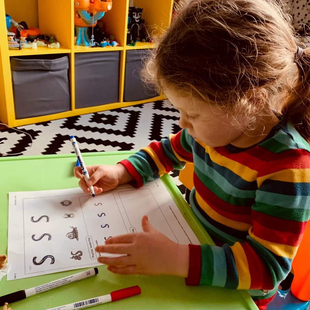 A preschooler practices writing the letter S