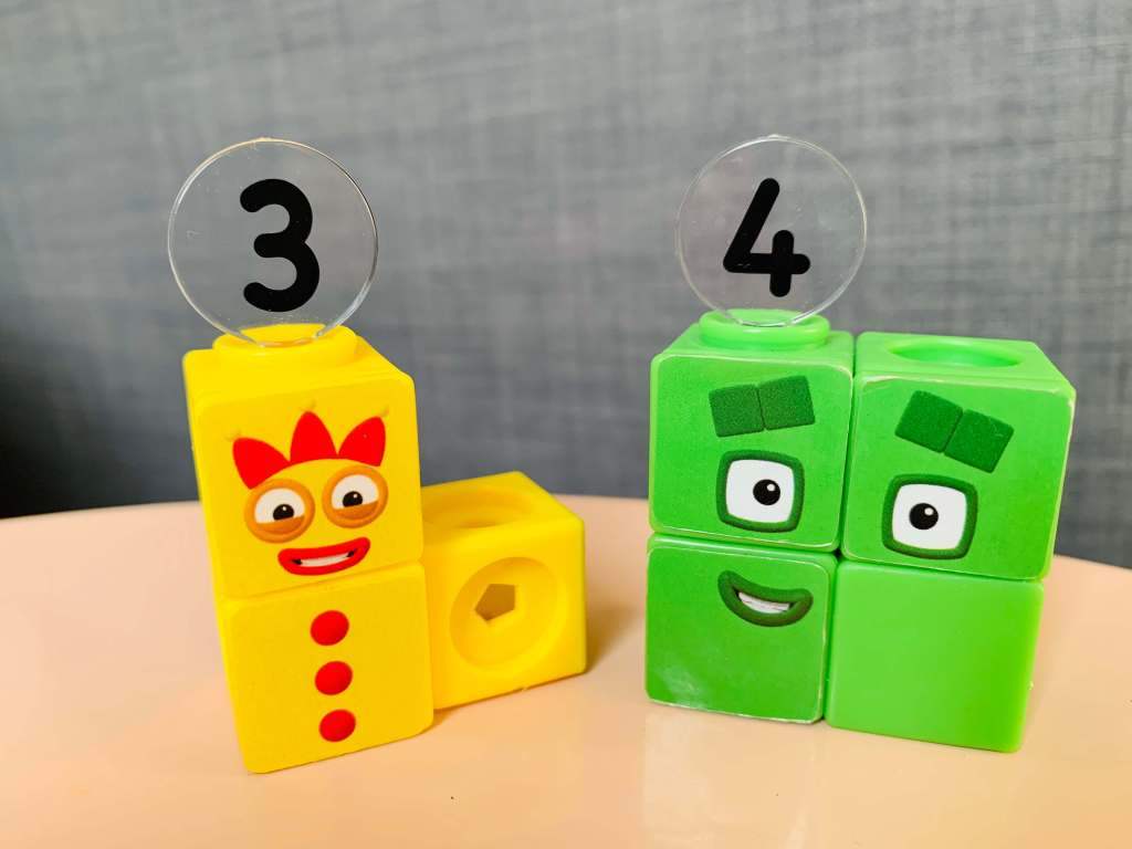Numberblocks Mathlinks cubes are shown configured for the number three (3) and four (4) to show the distinction between odd and even numbers