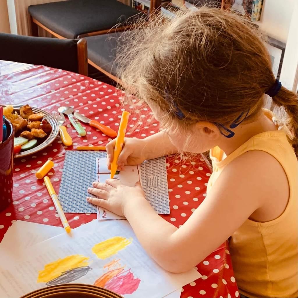 A preschooler practices her letter formation
