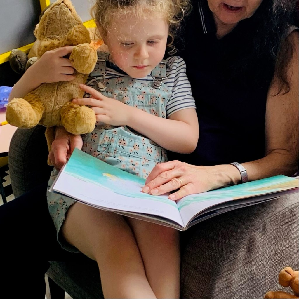 A young child sits on her grandmother's knee to share a picture book together