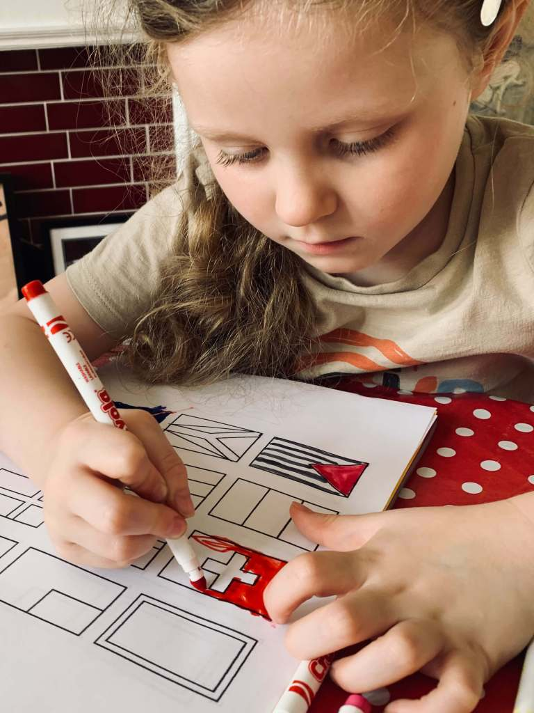 A preschool child uses a felt pen to colour in the national flags on a printable sheet of flags