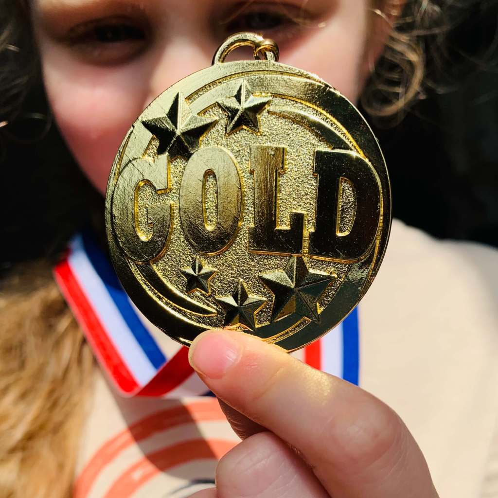 A preschool child holds up a pretend gold medal from her school sports day