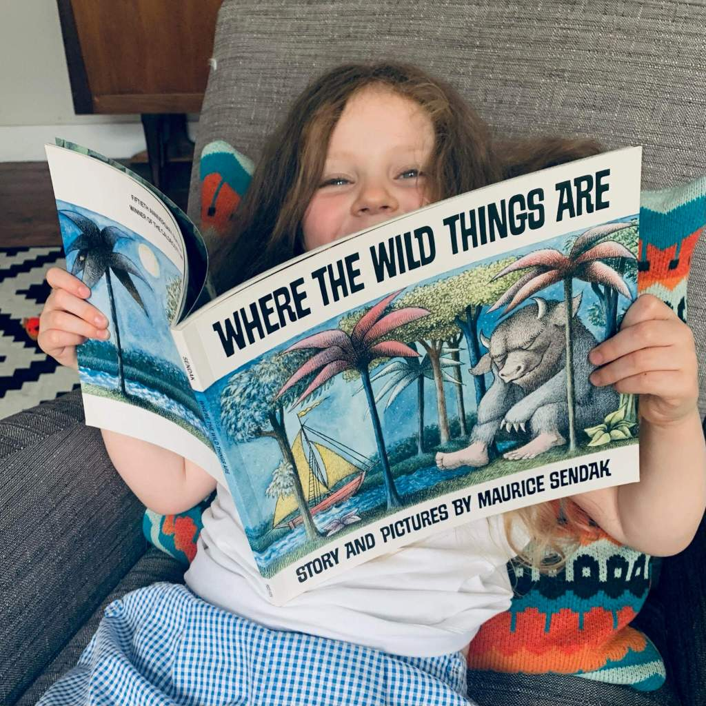 A young child peeks smilingly over the top of a copy of Maurice Sendak's Where the Wild Things Are
