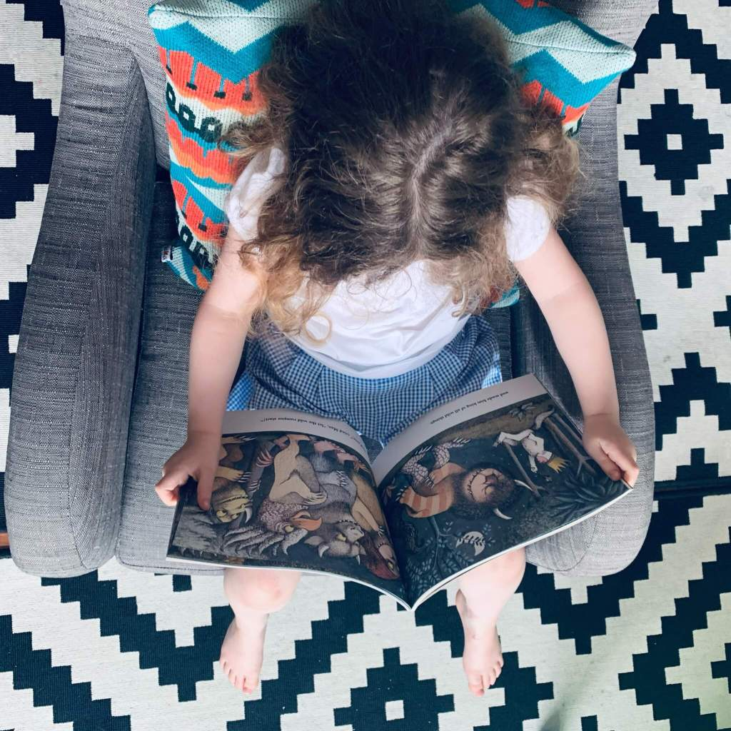 A young child reads a copy of Maurice Sendak's Where the Wild Things Are