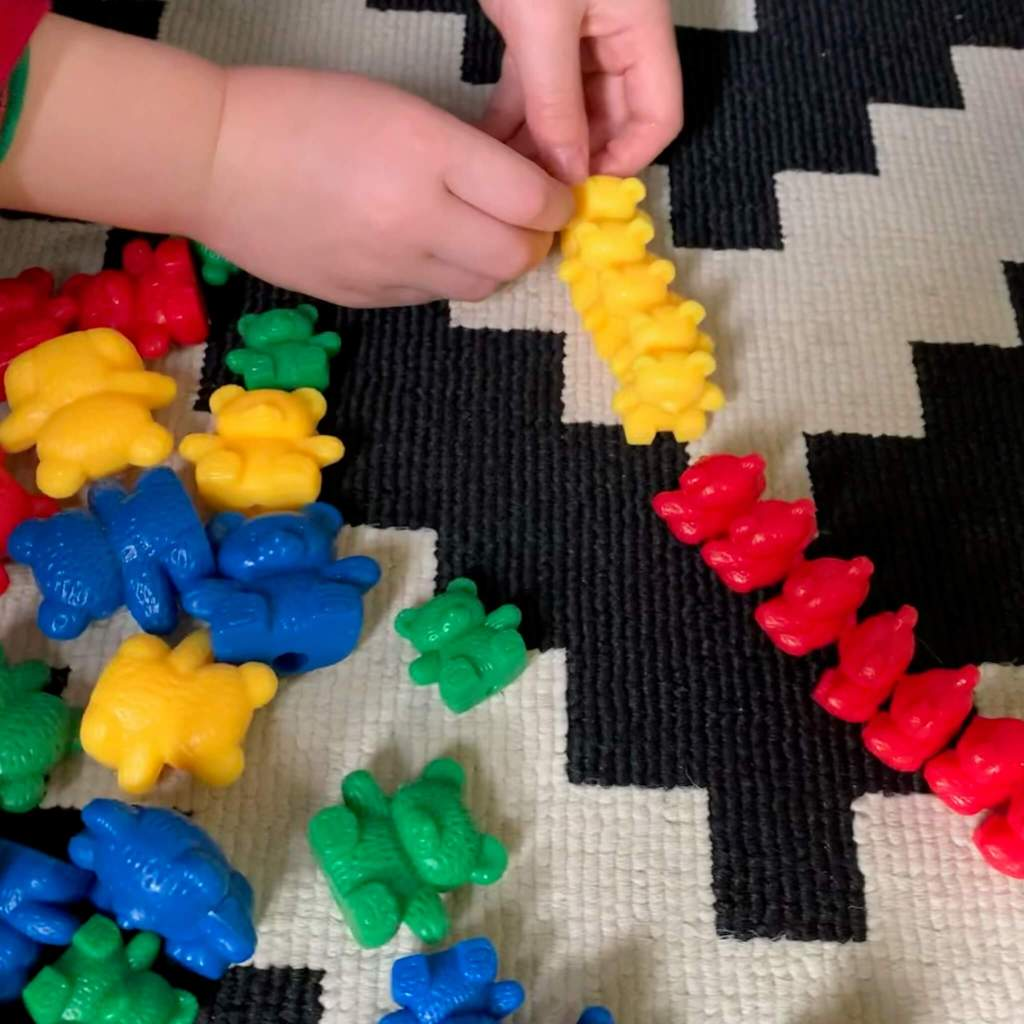 A child plays with a line of compare bears, sorting them into yellow and red groups